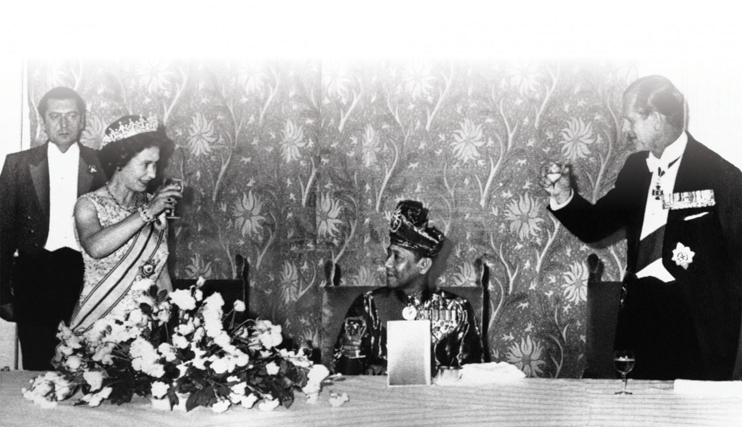 1974: Queen Elizabeth II of England and the Duke of Edinburgh toast the King of Malaysia, seated between them in evening on Thursday, July 12, 1974, at Claridges in London. The dinner marked the third day of the King and Queen of Malaysia's visit to England
